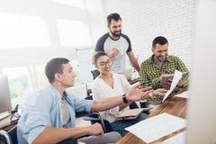 Работники офиса и персона в кресло-коляске обсуждают работать дела Они работают в ярком офисе Стоковые Изображения