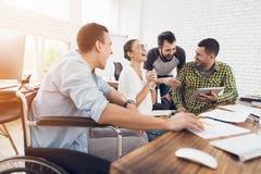 Работники офиса и персона в кресло-коляске обсуждают работать дела Они работают в ярком офисе Стоковые Изображения RF