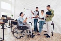 Работники офиса и человек в кресло-коляске обсуждая моменты дела пока работающ в современном офисе Стоковое Изображение RF