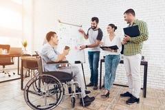 Работники офиса и человек в кресло-коляске обсуждая моменты дела пока работающ в современном офисе Стоковые Изображения RF