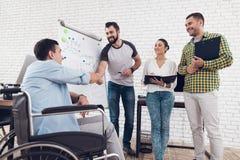 Работники офиса и человек в кресло-коляске обсуждая моменты дела пока работающ в современном офисе Стоковая Фотография