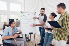 Работники офиса и человек в кресло-коляске обсуждая моменты дела пока работающ в современном офисе Стоковое Фото