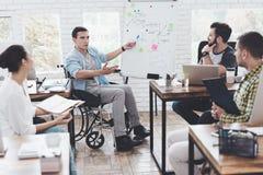 Работники офиса и человек в кресло-коляске обсуждая моменты дела в современном офисе Стоковые Фото