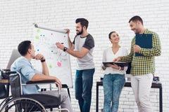 Работники офиса и человек в кресло-коляске обсуждая моменты дела в современном офисе Стоковая Фотография RF