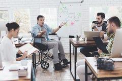 Работники офиса и человек в кресло-коляске обсуждая моменты дела в современном офисе Стоковые Изображения RF