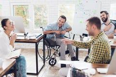 Работники офиса и человек в кресло-коляске обсуждая моменты дела в современном офисе Стоковое Фото