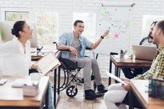Работники офиса и человек в кресло-коляске обсуждая моменты дела в современном офисе Стоковое Изображение RF