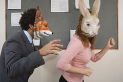 Работники офиса околпачивая вокруг в масках стоковое фото