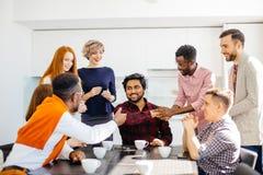 Работники офиса приветствуют индийского рекламодателя с улыбкой стоковое фото