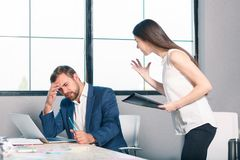 Работники офиса присягают, клекоты девушки на человеке который слабонервно льнет к его голове Внутри офиса Стоковые Фотографии RF