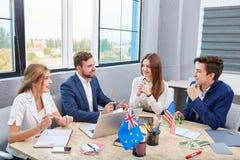 Работники офиса сидят на таблице и говорят Стоковые Изображения
