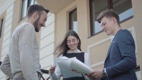 Работники портрета 3 молодые обсуждают проект пока держащ бумаги или документы outdoors Успешное уверенное видеоматериал