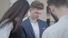 Работники портрета 3 молодые обсуждают проект пока держащ бумаги или конец-вверх документов outdoors Успешный видеоматериал