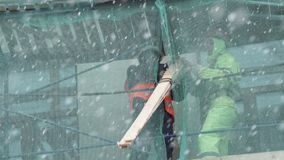 Работники построителей стоят на лесах конструкции и вытягивают вверх по деревянным планкам сток-видео
