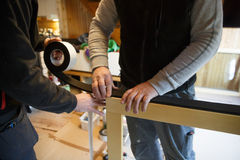 Работники подготавливая установить новые деревянные окна стоковое фото