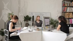 Работники работают в творческом офисе на их настольных компьютерах и компьютерах видеоматериал