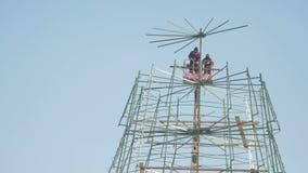 Работники работают строительство в высоком месте - делающ сосну Нового Года для отпразднуйте сток-видео