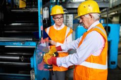 Работники работая машины на современной фабрике Стоковое Фото