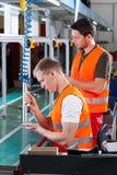 Работники работая рядом с машиной Стоковые Изображения