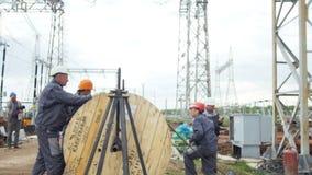 Работники раскручивают кабель от катушкы на электрической подстанции сток-видео