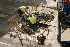 Работники ремонтируя сломленную трубу водопровода на дороге стоковое изображение