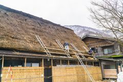 Работники ремонтируя соломенную крышу дома Gassho, Shirakawa Стоковые Изображения RF
