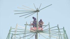 Работники ремонтируя строительство в высоком месте - делающ сосну Нового Года для отпразднуйте сток-видео