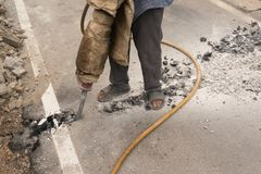 Работники сверлят дорогу к трубе водопровода после не координировать с отделом шоссе стоковое фото
