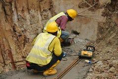 Работники сверля бетон используя передвижную сверля машину Стоковое Изображение