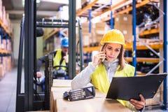 Работники склада при smartphone работая совместно стоковое фото rf