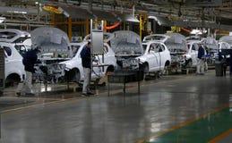 Работники собирают автомобиль на сборочном конвейере в фабрике автомобиля стоковые изображения rf
