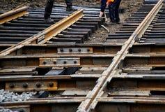 Работники собирают деревянные слиперы и рельсы трамвая во время ремонта дорог города стоковое фото