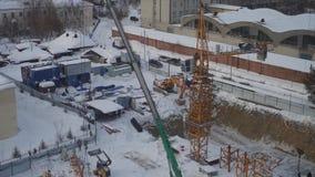 Работники собирают кран конструкции зимы на том основании, и после этого поднимают часть на веревочках, TimeLapse акции видеоматериалы