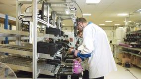 Работники собирают метры в розовых случаях на линии сток-видео