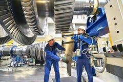 Работники собирая и строя газовые турбины в современном ind стоковая фотография