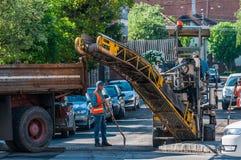 Работники строительства дорог очищая улицу стоковая фотография
