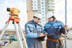 Работники съемщика с уровнем на строительной площадке Стоковые Фото
