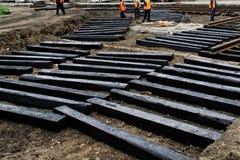 Работники устанавливают в слиперы черноты канавы деревянные для рельсов трамвая Ремонт дороги города стоковые фото