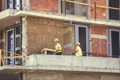 Работники устанавливают изоляцию минеральных шерстей утеса на внешнюю стену 2 стоковая фотография