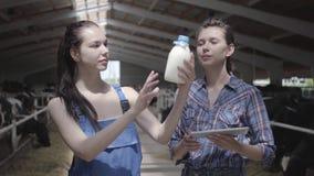 Работники фермера портрета 2 профессиональные милые женские на ферме коровы проверяя качество молока в бутылке Одно видеоматериал