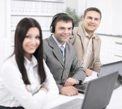 Работники центра телефонного обслуживания сидя на их столе стоковое фото
