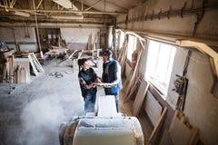 Работники человека и женщины в мастерской плотничества держа древесину Стоковое фото RF