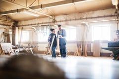 Работники человека и женщины с таблеткой в мастерской плотничества Стоковые Фото