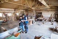 Работники человека и женщины с таблеткой в мастерской плотничества Стоковое Изображение