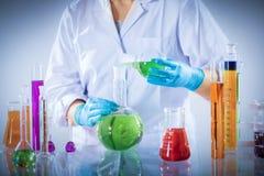 Работник лаборатории смешивает химический жидкостный образец стоковая фотография rf