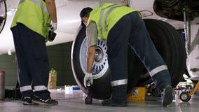 Работник авиапорта проверяя шасси Двигатель и шасси самолета пассажира под тяжелым обслуживанием Проверки инженера Стоковая Фотография RF