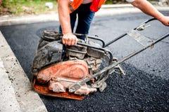 Работник асфальта на месте строительства дорог с comp Стоковое Фото
