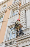 Работник альпиниста восстанавливая фасад здания Будапешт, Венгрия Стоковые Фото