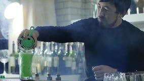 Работник бара с бородой льет свеже сжиманный сок от шейкера в большое стекло в светлом помохе сток-видео