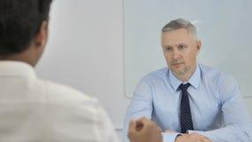 Работник бизнесмена волос серого цвета слушая на работе, обсуждая работу